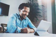 Giovane uomo africano sorridente che fa video conversazione tramite compressa digitale con gli amici mentre sedendosi alla tavola Immagine Stock