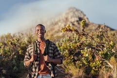 Giovane uomo africano sorridente che gode di un viaggio nelle montagne Fotografia Stock Libera da Diritti