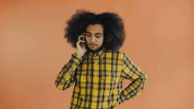Giovane uomo afroamericano attraente felice che parla sul telefono cellulare su fondo arancio Concetto delle emozioni stock footage