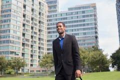 Giovane uomo afroamericano bello che cammina per lavorare, guardando raggiro Immagini Stock Libere da Diritti