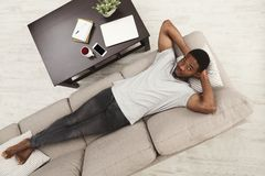 Giovane uomo afroamericano bello che si rilassa sullo strato a casa fotografia stock libera da diritti