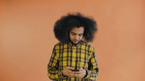 Giovane uomo afroamericano bello facendo uso del telefono su fondo arancio Concetto delle emozioni video d archivio