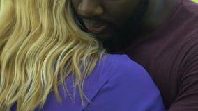 Giovane uomo afroamericano che abbraccia donna caucasica per sostenerla, primo piano stock footage