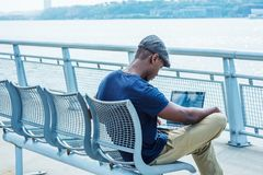 Giovane uomo afroamericano che lavora al computer portatile all'aperto dentro Fotografie Stock