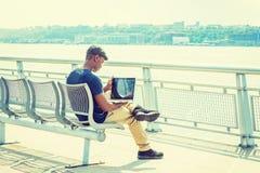 Giovane uomo afroamericano che lavora al computer portatile all'aperto dentro Immagine Stock Libera da Diritti
