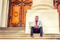 Giovane uomo afroamericano che lavora al computer portatile fuori dentro Fotografia Stock