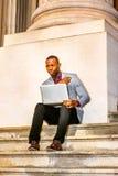 Giovane uomo afroamericano che lavora al computer portatile fuori dentro Fotografia Stock Libera da Diritti