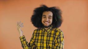 Giovane uomo afroamericano che mostra gesto di bla di bla o di silenzio su fondo arancio Concetto delle emozioni video d archivio