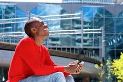Giovane uomo afroamericano che ride fuori con il telefono cellulare Fotografia Stock Libera da Diritti