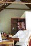 Giovane uomo afroamericano che si siede alla tavola con il telefono cellulare Immagine Stock Libera da Diritti