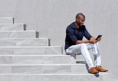 Giovane uomo afroamericano che si siede sui punti facendo uso della compressa Immagini Stock Libere da Diritti