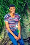 Giovane uomo afroamericano che vi manca con la rosa di bianco, aspettante Immagine Stock