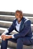 Giovane uomo afroamericano di affari che si siede sui punti all'aperto e sul sorridere Immagine Stock Libera da Diritti