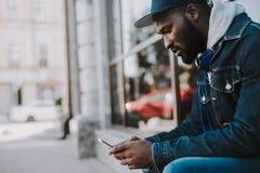 Giovane uomo afroamericano disturbato che legge un messaggio immagini stock libere da diritti