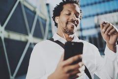 Giovane uomo afroamericano felice in cuffia che cammina alla città soleggiata e che gode di ascoltare musica sul suo telefono cel Fotografie Stock Libere da Diritti