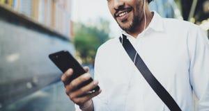 Giovane uomo afroamericano felice in cuffia che cammina alla città soleggiata e che gode di ascoltare musica sul suo telefono cel Fotografia Stock