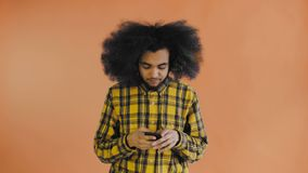 Giovane uomo afroamericano frustrato che tiene telefono cellulare rotto su fondo arancio Concetto delle emozioni archivi video