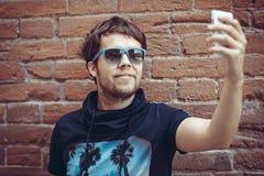Giovane uomo alla moda barbuto dei pantaloni a vita bassa che fa selfie con il telefono Immagine Stock