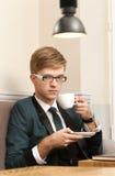 Giovane uomo alla moda bello in caffè con caffè Immagine Stock