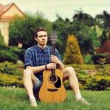 Giovane uomo alla moda dei pantaloni a vita bassa con la chitarra nel parco Fotografia Stock Libera da Diritti