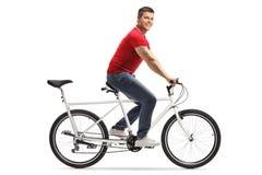 Giovane uomo allegro che guida una bicicletta in tandem da solo e che sorride alla macchina fotografica immagine stock libera da diritti