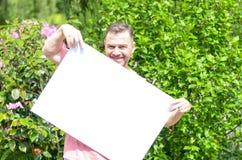 Giovane uomo allegro che mostra una lavagna in bianco Fotografia Stock Libera da Diritti
