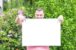 Giovane uomo allegro che mostra una lavagna in bianco Immagini Stock Libere da Diritti