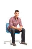 Giovane uomo allegro che si siede su una sedia fotografia stock