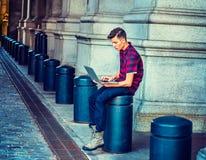 Giovane uomo americano che lavora al computer sulla via a New York Fotografia Stock