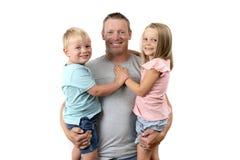 Giovane uomo americano felice ed attraente che tiene i suoi due bambini derivato adorabile di 7 anni un bello ed i suoi piccoli 3 Immagine Stock