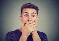 Giovane uomo ansioso con il fronte spaventato colpito che esamina macchina fotografica Immagini Stock
