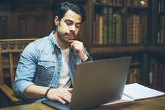 Giovane uomo arabo che lavora con il computer portatile in biblioteca Immagini Stock Libere da Diritti