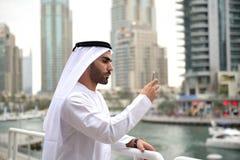 Giovane uomo arabo di Emirati che fa una pausa il canale Immagini Stock