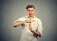 Giovane uomo arrabbiato che mostra gesto di mano di tempo fuori Immagine Stock Libera da Diritti
