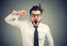 Giovane uomo arrabbiato di affari che accusa qualcuno che grida immagine stock