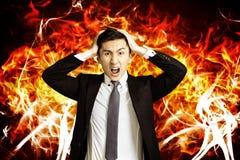 Giovane uomo arrabbiato di affari con il fondo del fuoco di combustione immagini stock