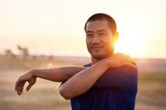 Giovane uomo asiatico adatto che allunga le sue armi prima di un funzionamento Immagine Stock Libera da Diritti