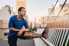 Giovane uomo asiatico adatto che allunga prima di un funzionamento urbano Fotografia Stock Libera da Diritti