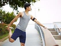 Giovane uomo asiatico atletico che allunga gamba all'aperto Fotografie Stock Libere da Diritti