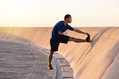 Giovane uomo asiatico atletico che allunga le sue gambe prima di un funzionamento Immagine Stock Libera da Diritti