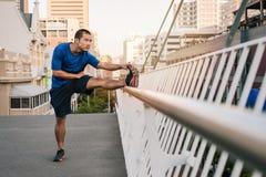 Giovane uomo asiatico atletico che allunga prima di un funzionamento della città Fotografia Stock Libera da Diritti