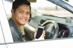 Giovane uomo asiatico attraente che sorride e che esamina macchina fotografica mentre mostrando il suo smartphone alla macchina f immagini stock libere da diritti
