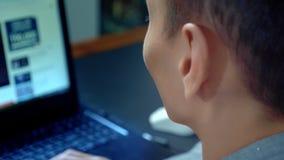 Giovane uomo asiatico bello facendo uso del suo computer portatile, sedentesi allo scrittorio in ufficio video d archivio