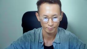 Giovane uomo asiatico bello facendo uso del suo computer portatile, sedentesi allo scrittorio in ufficio archivi video