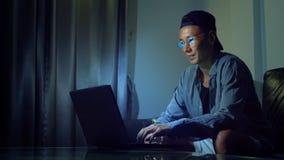 Giovane uomo asiatico bello in vetri con le riflessioni facendo uso del suo computer portatile, sedentesi nella sera nella stanza stock footage