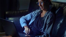 Giovane uomo asiatico bello in vetri con le riflessioni facendo uso del suo computer portatile, sedentesi nella sera nella stanza video d archivio