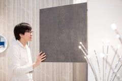 Giovane uomo asiatico che apre guardaroba moderno che sceglie mobilia in wa immagine stock