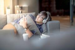 Giovane uomo asiatico che ascolta la musica, avendo a sul sofà Immagini Stock