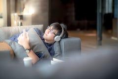 Giovane uomo asiatico che ascolta la musica, avendo un pelo sul sofà Fotografia Stock