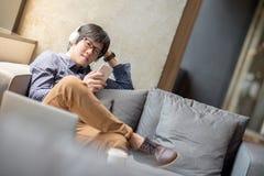 Giovane uomo asiatico che ascolta la musica facendo uso dello smartphone sul sofà Fotografia Stock